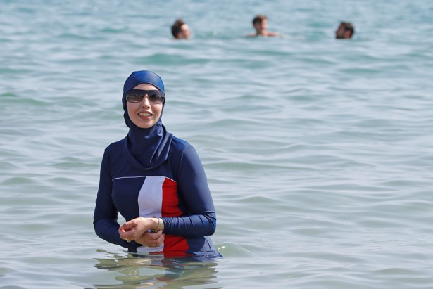 A woman in a tri-color burkini swims in the ocean in Cannes, France.