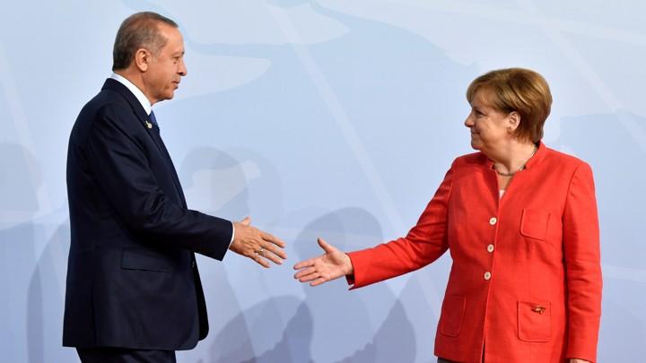 German Chancellor Angela Merkel greets Turkey's President Recep Tayyip Erdogan shake hands on stage at the G20.