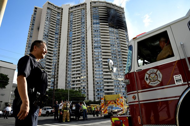 A police officer directs a fire truck at the Marco Polo apartment building after a fire broke out in it in Honolulu, Hawaii.