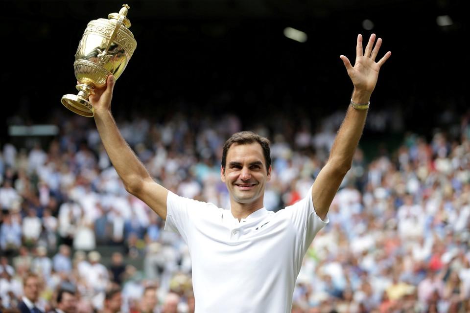 Roger Federer shows off his Wimbledon trophy.