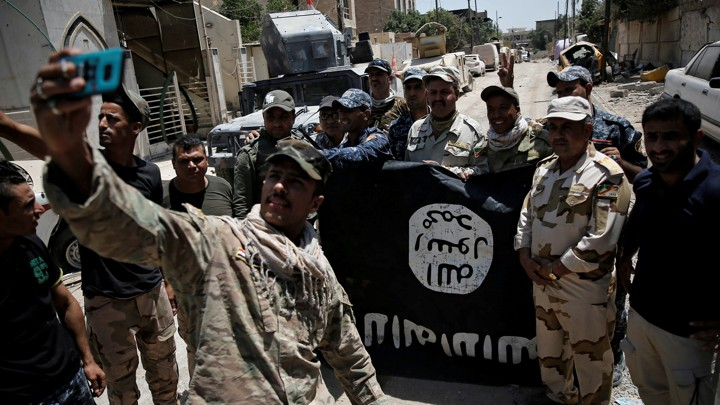 Iraqi soldiers take a selfie in front of an Islamic State flag captured during the battle to reclaim Mosul.