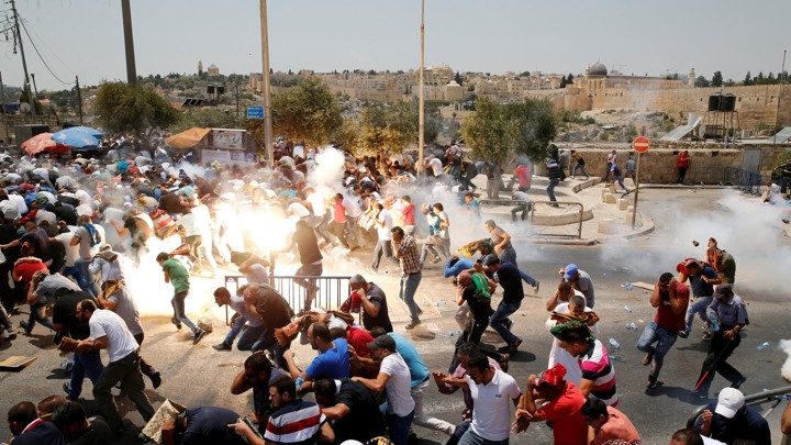Palestinians react following tear gas that was shot by Israeli forces after Friday prayer on a street outside Jerusalem's Old city .