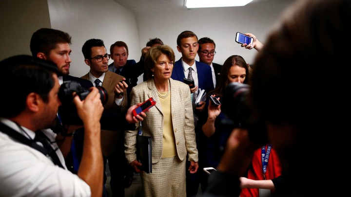 Senator Lisa Murkowski stands with reporters on Capitol Hill.