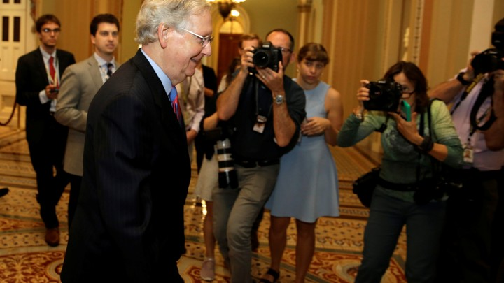 Senate Majority Leader Mitch McConnell walks down a hallway in a Capitol Hill building.