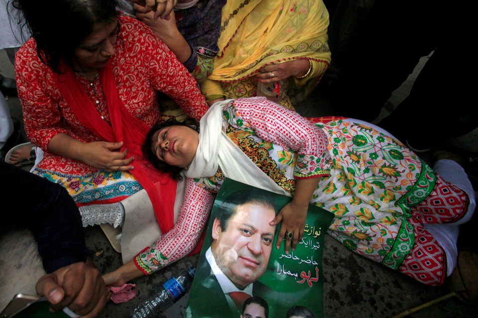 A supporter of Pakistan's Prime Minister Nawaz Sharif passes out on the ground, holding a photo of him.