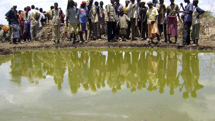 A group of people gather around a small, cloudy body of water.