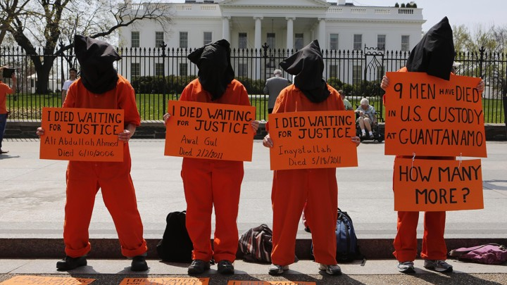 Four activists dressed up as Guantanamo Bay prisoners in front of the White House hold signs that accuse the U.S. administration of ignoring the deaths of prisoners waiting to be released from the U.S. prison in Cuba.