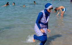 A woman wearing a burqini walks in the water on a beach in France.