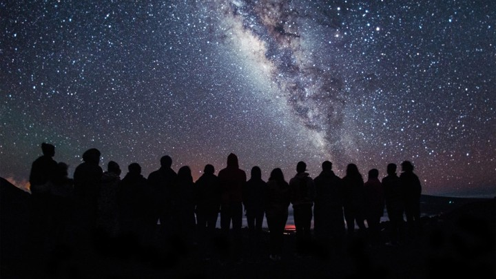 A group of people standing silhouetted against a star-filled sky