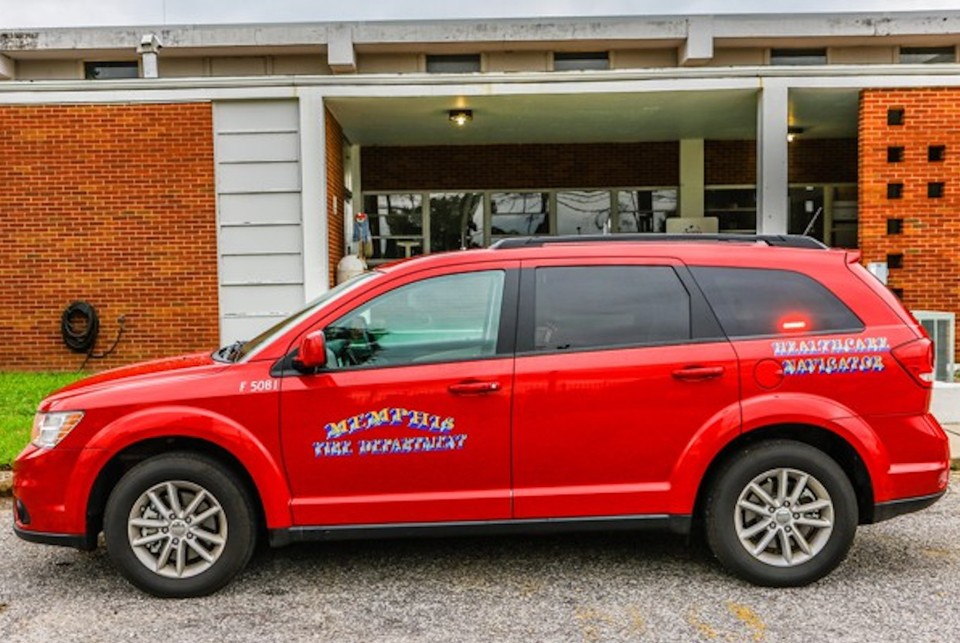 "A red SUV with ""Memphis Fire Department"" and ""Healthcare Navigator"" printed on the side of the vehicle"