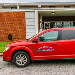 """A red SUV with """"Memphis Fire Department"""" and """"Healthcare Navigator"""" printed on the side of the vehicle"""