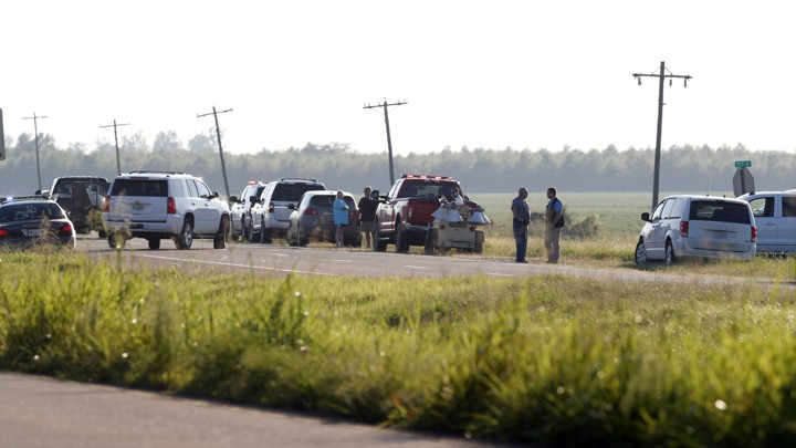 Emergency personnel stand along U.S. Highway 82 following the plane crash on July 10, 2017.