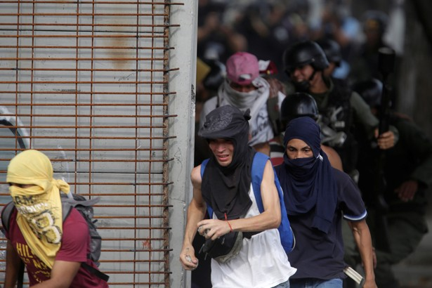 Demonstrators run away from security forces at a rally in Caracas on July 27, 2017.