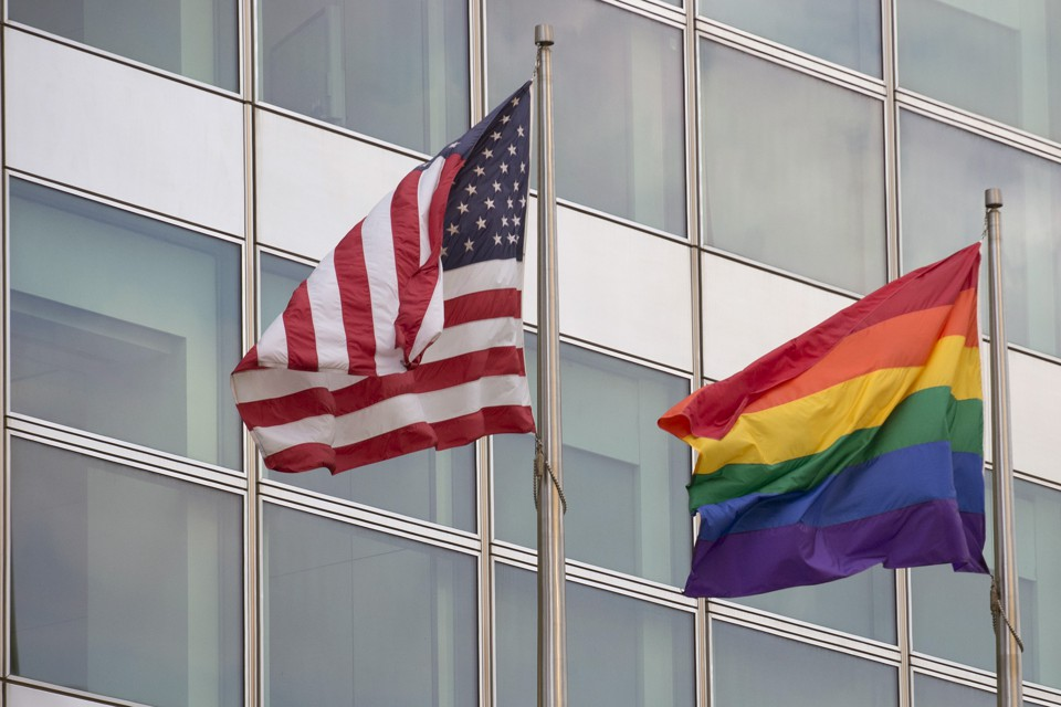 An American flag and a rainbow pride flag are pictured next to each other.