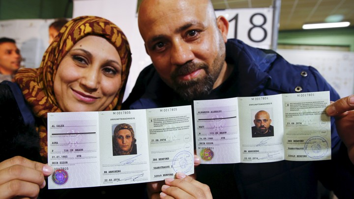 A Syrian couple presents their newly issued German registration documents.