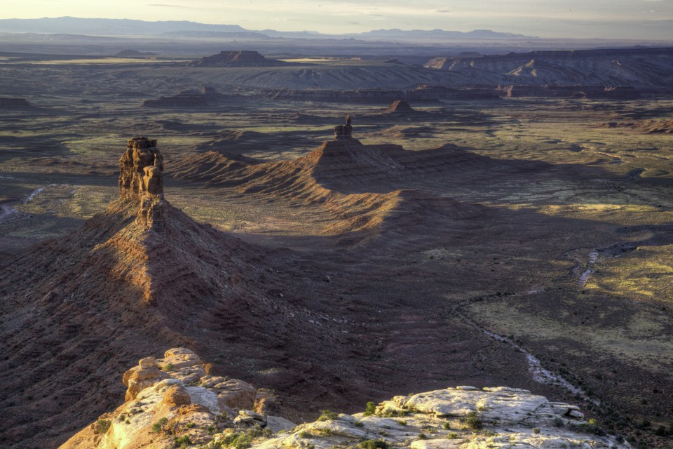 Cedar Mesa Valley of the Gods in Utah. Rock formations rise out of red soil.