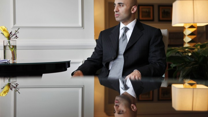 United Arab Emirates Ambassador to the U.S. Yousef al Otaiba, sits on a table and stares out the window.