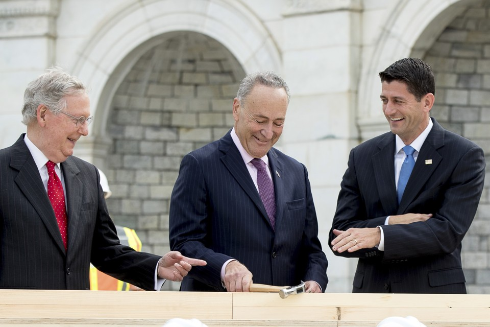 House Speaker Paul Ryan, right, and Senate Majority Leader Mitch McConnell, left, laugh at Senator Charles Schumer during a ceremony to drive in the first nails to signify the start of construction on the 2017 presidential inaugural platform on Capitol Hill in Washington.