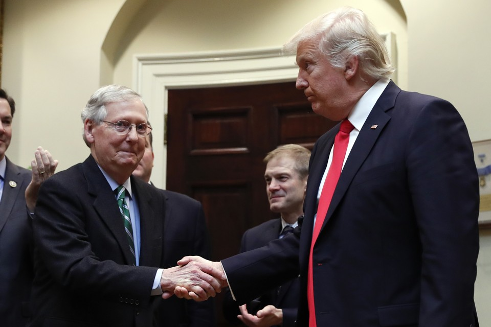 Mitch McConnell and President Trump shake hands.