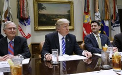 President Trump sits at a table with Paul Ryan and Mitch McConnell