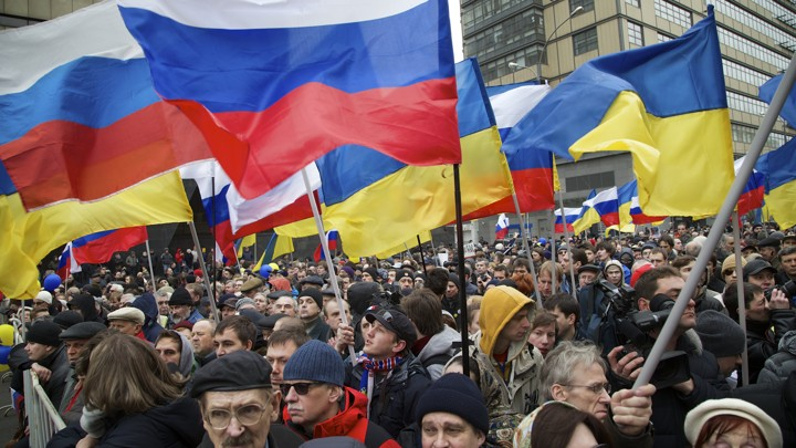 Demonstrators hold Russian and Ukrainian flags.