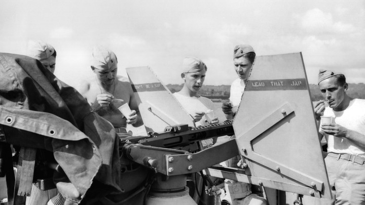 Young American soldiers in the South Pacific stand behind an anti-aircraft gun while eating ice cream, 1943
