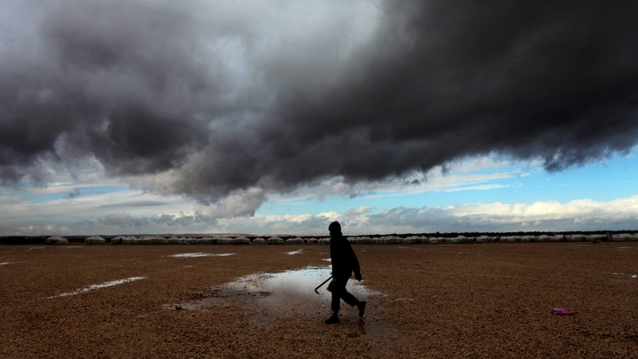 A Syrian refugee walks toward his tent at Zaatari refugee camp through puddles and in front of storm clouds.