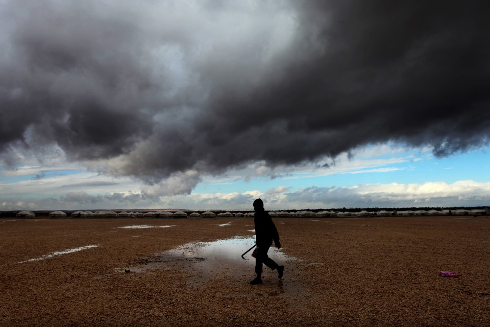 A Syrian refugee walks toward his tent at Zaatari refugee camp through puddles and in front