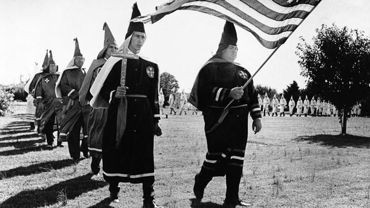 Ku Klux Klan members march in cemetery funeral rites in Chesapeake, Virginia, in 1966.
