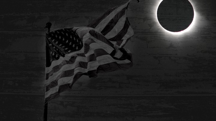 A flag waves in the dark, with a full eclipse in the background