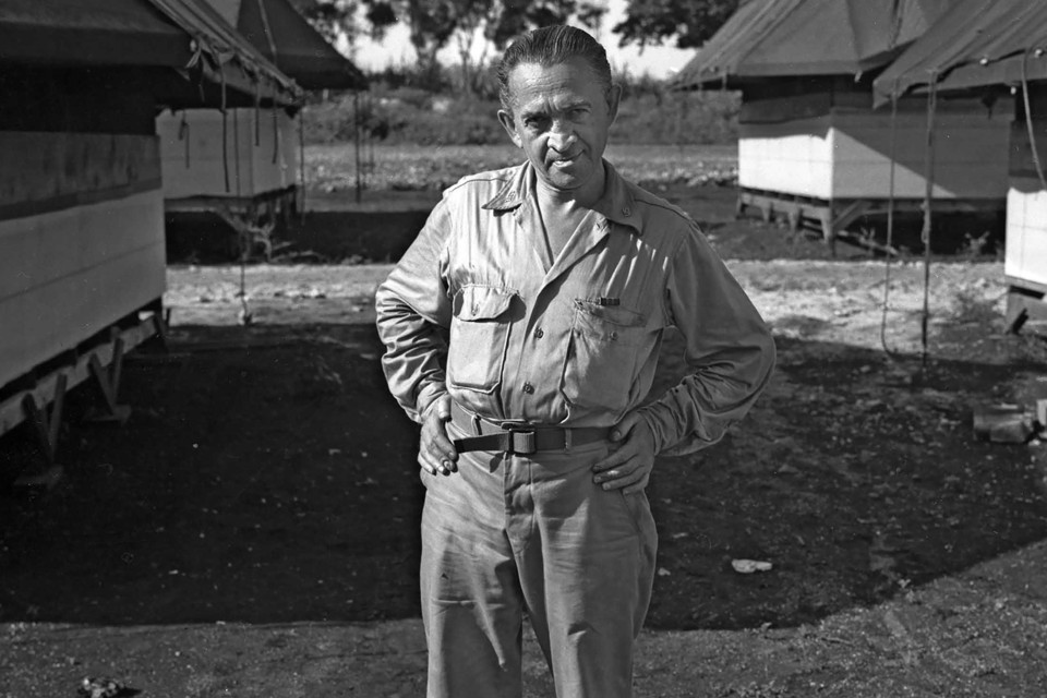 "William L. ""Atomic Bill"" Laurence standing with hands on hips at Tinian Island in the Pacific, the launching point for the atomic bomb attacks against Hiroshima and Nagasaki"