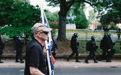 """A white nationalist is seen leaving Emancipation Park in Charlottesville, Virginia, where violent clashes took place between counter-protesters and white-nationalist groups. Hundreds of white nationalist gathered at the park for a """"Unite The Right"""" rally to protest the removal of the statue of Robert E. Lee, which is seen in the background."""