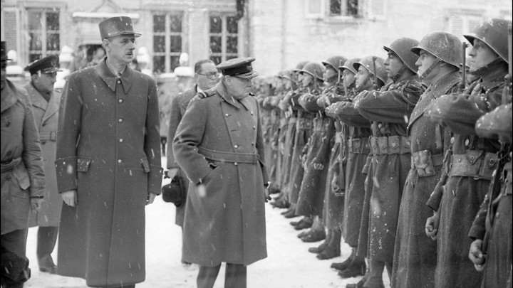 Winston Churchill and General De Gaulle walk past assembled French soldiers under a snowstorm.