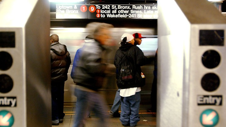 People standing on a subway platform in New York City, framed by two turnstiles