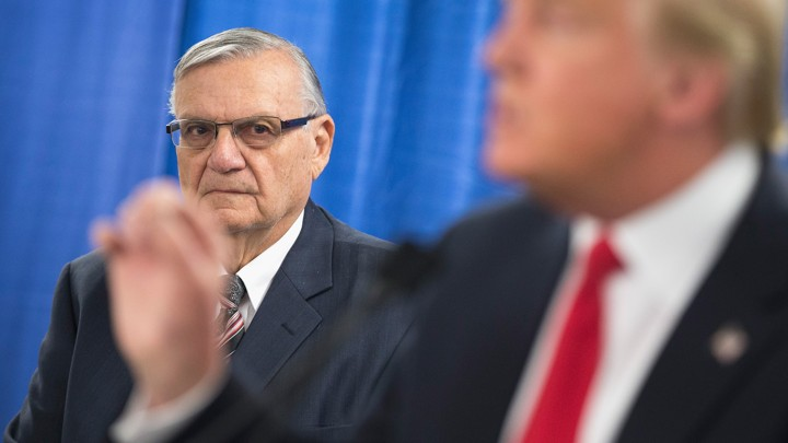 Former Maricopa County Sheriff Joe Arpaio looks on as then-presidential candidate Donald Trump speaks to reporters.