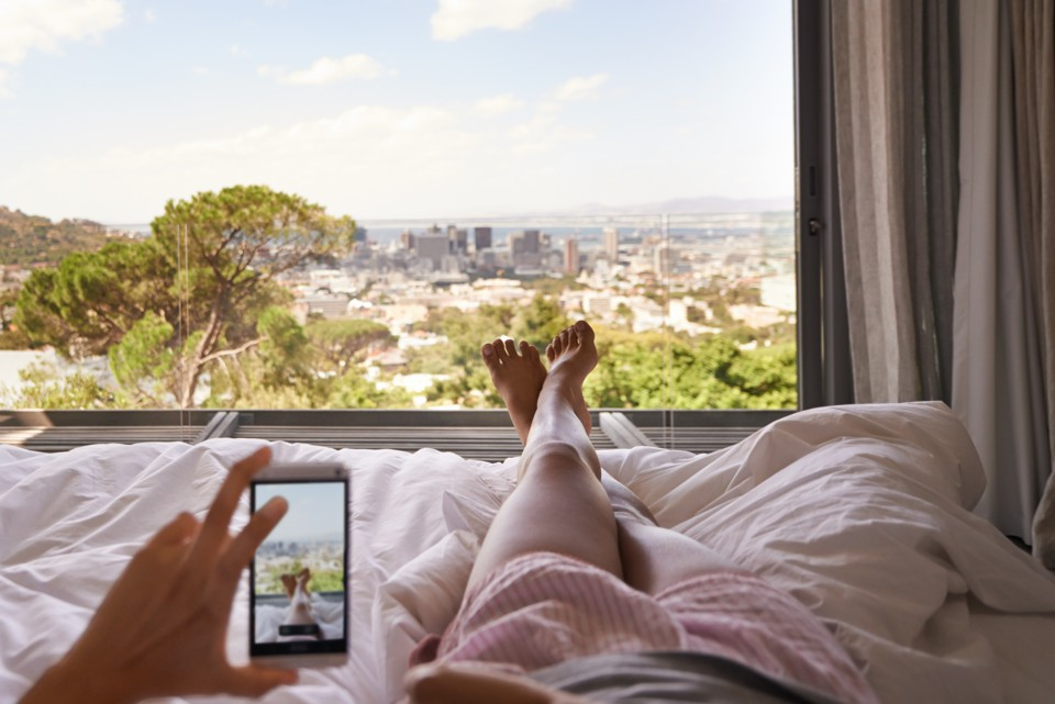 A woman takes a picture of herself lying in bed, overlooking city in the distance