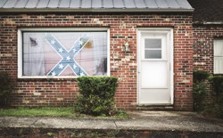 A Confederate flag hangs in the window of a house.