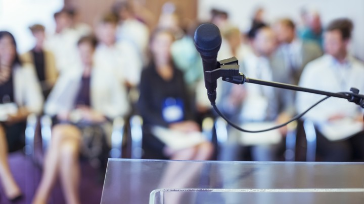 Close-up of microphone and transparent lectern with audience seen in blurred background