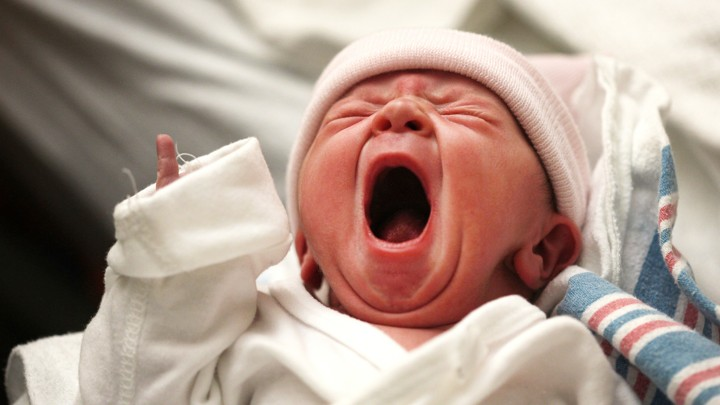 A baby yawns in a hospital.