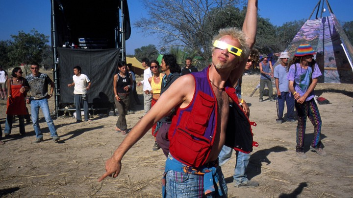 A man wearing eclipse glasses and colorful clothing gestures upward.