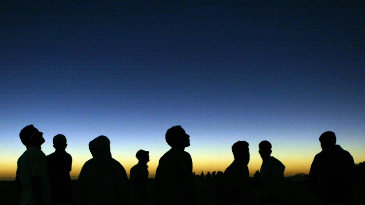 Libyan youths watch the solar eclipse in the desert tourist camp in Galo.