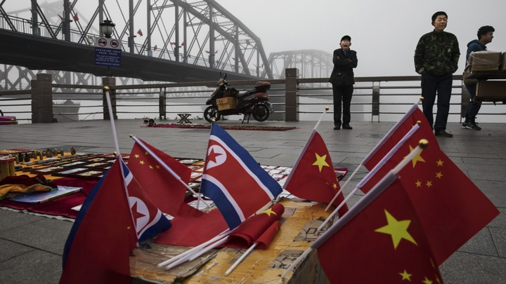 Chinese vendors sell North Korea and China flags on the boardwalk next to a bridge that connects China and North Korea.