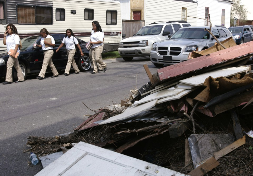 Students walk next to a pile of debris.
