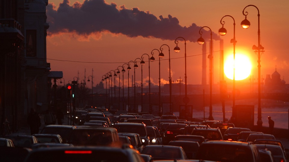 Pipes of a thermal power plant are seen during sunset, with cars stuck in a traffic jam in the foreground.