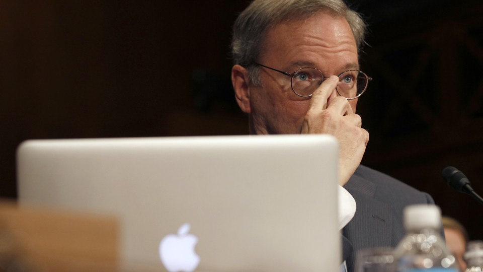 A man sitting behind an Apple laptop covers the lower half of his face with his hand.