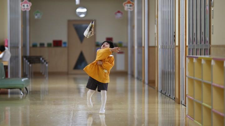 A boy plays in the hallway of a school in Japan
