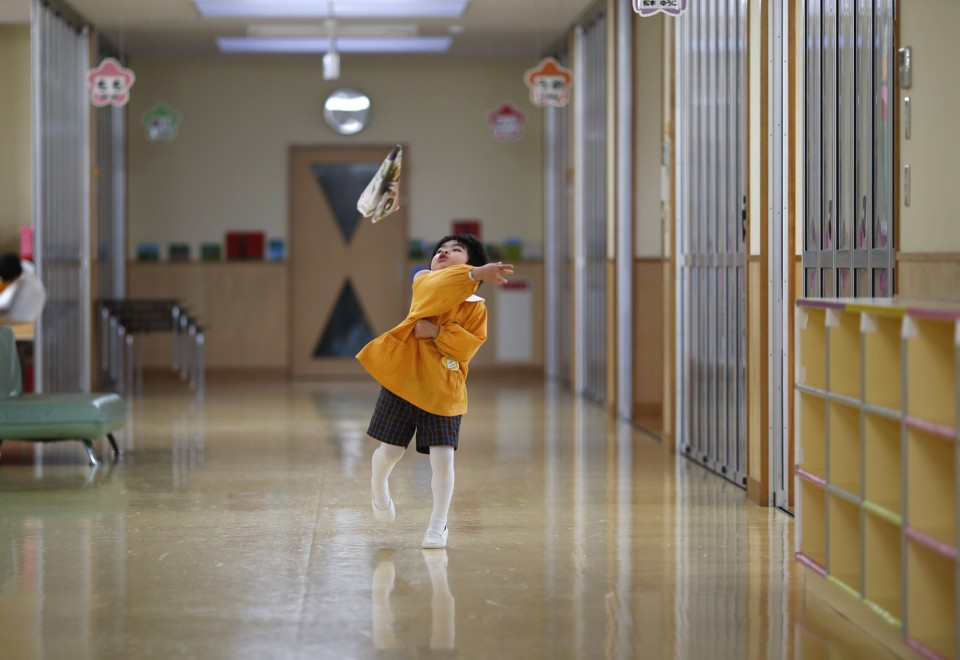 A boy plays in the hallway of a school in Japan