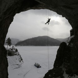 A climber belays from the top of a tall cave.