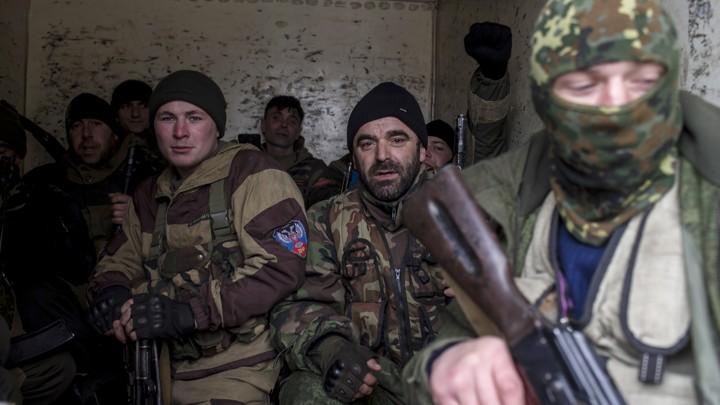 Pro-Russian rebels sit inside a truck, holding guns.