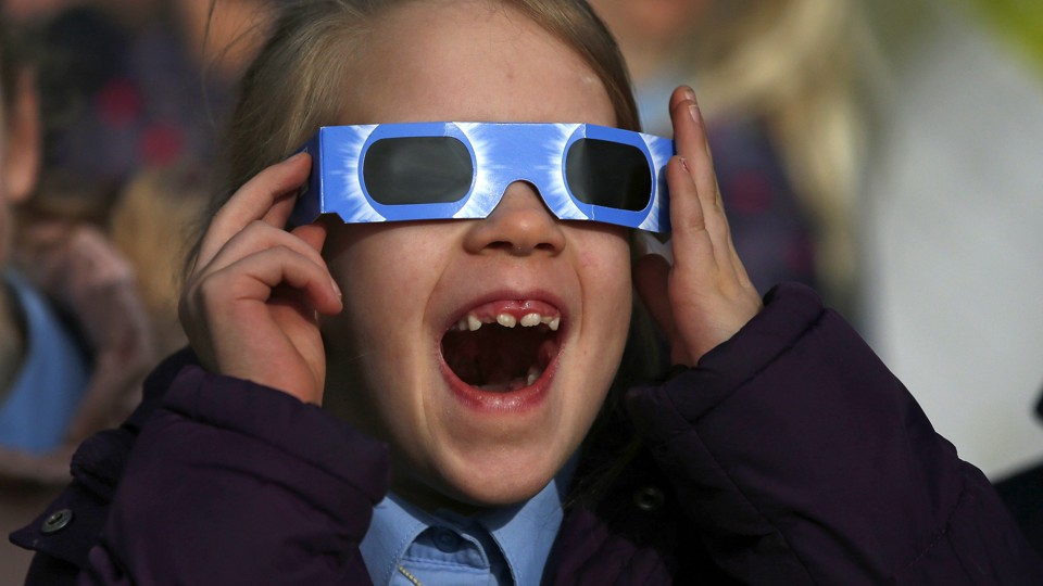A pupil wears protective glasses as she views a partial solar eclipse from a school in Altrincham.